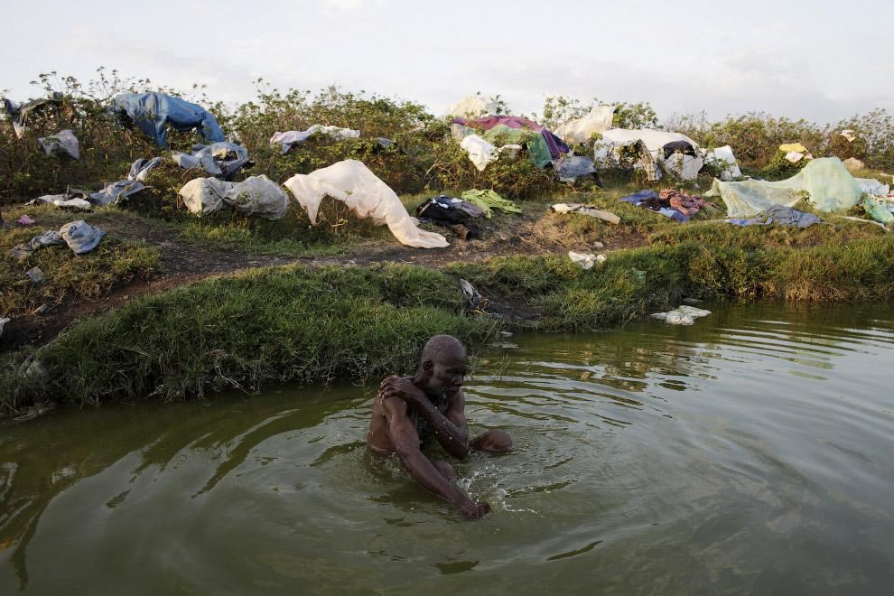 Прием ванны в грязном пруду недалеко от Порт-о-Пренс