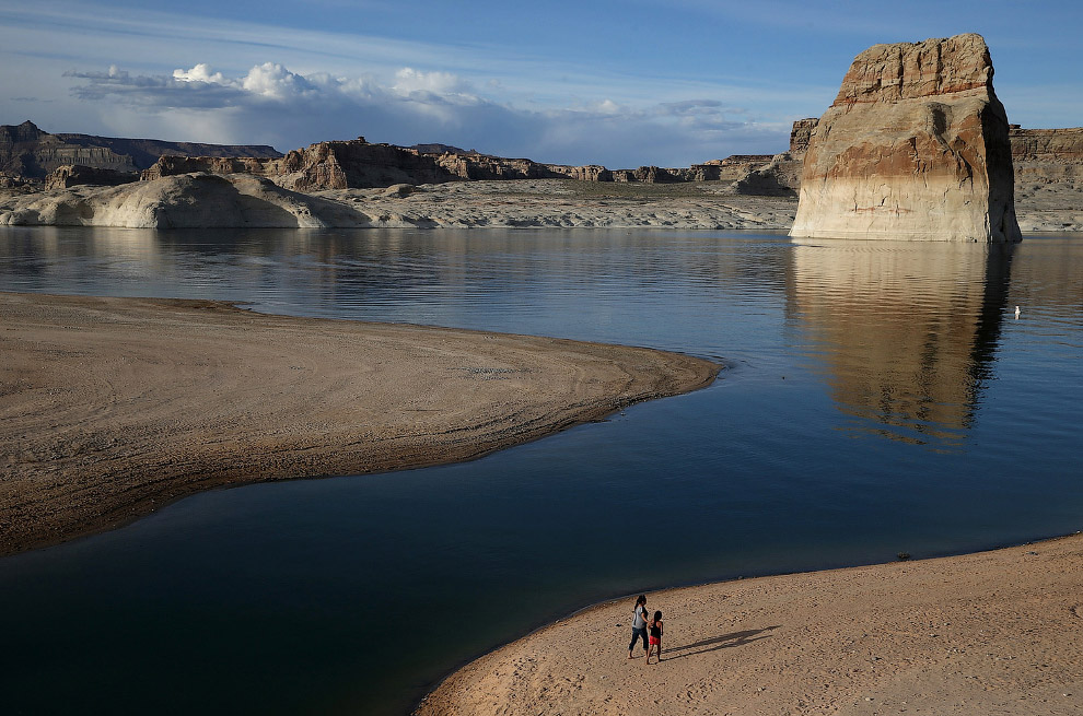 Люди ходят по пляжу, который когда-то был дном водохранилища Пауэлл, штат Юта