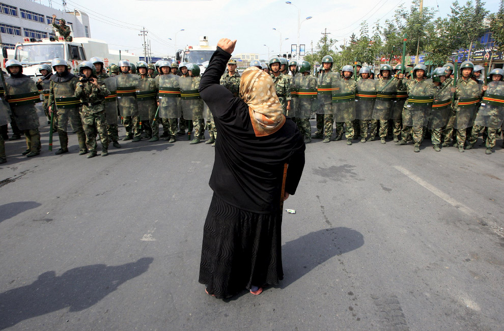 Местные жители противостоят силам безопасности на улице в городе Урумчи, Китай