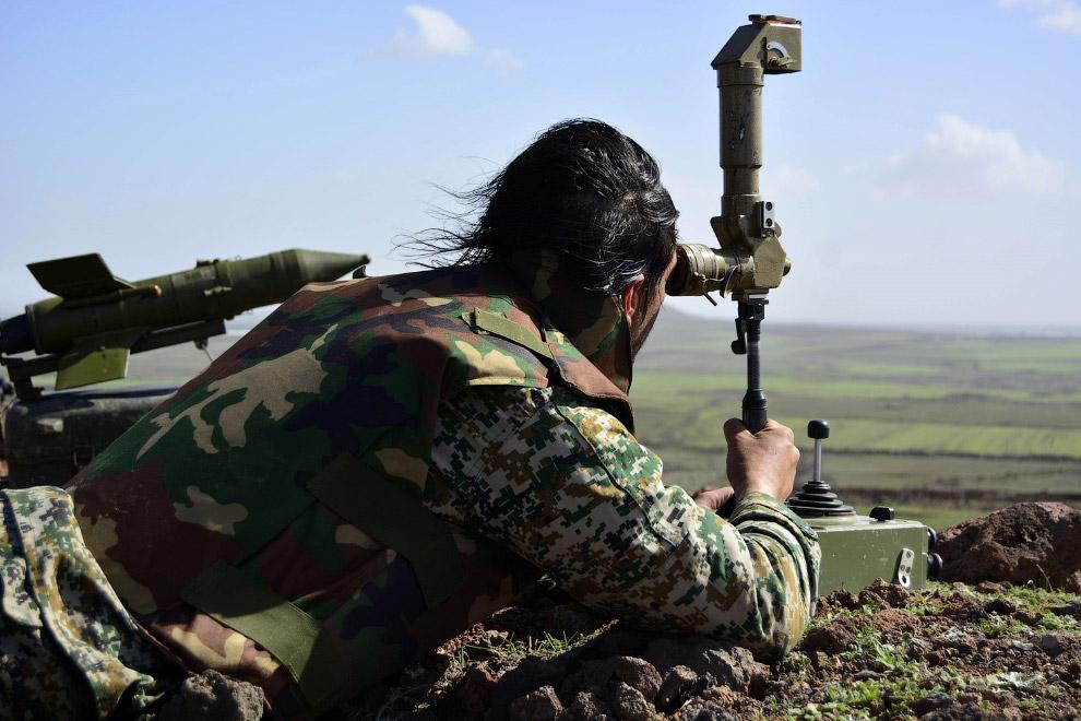 Солдат правительственных войск смотрит на вражеские позиции