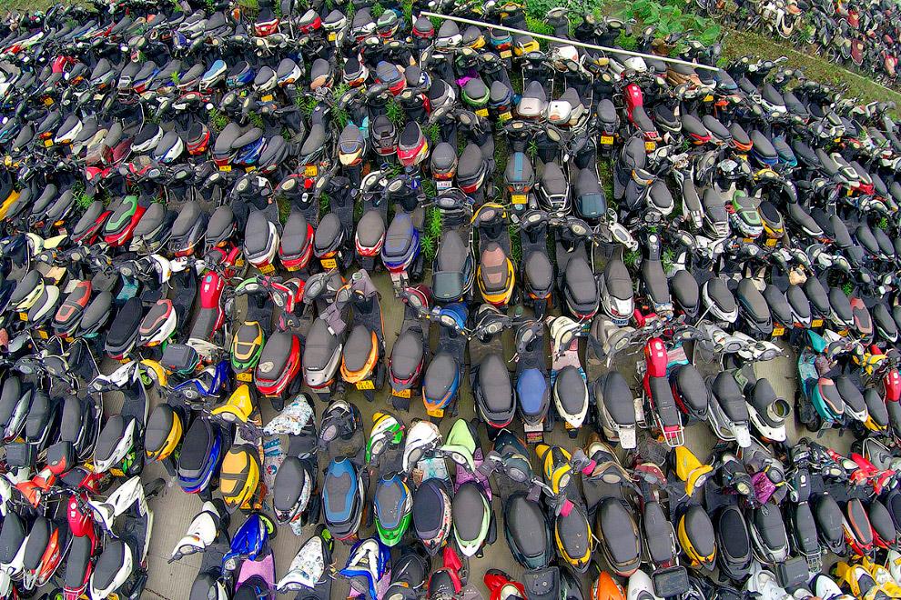 Стройными рядами стоят непригодные  для езды мотороллеры в городе Ханчжоу