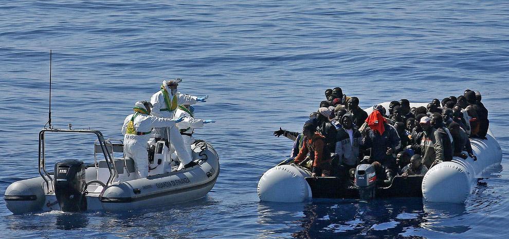 Судно с мигрантами и итальянская береговая охрана у берегов Ливии в Средиземном море
