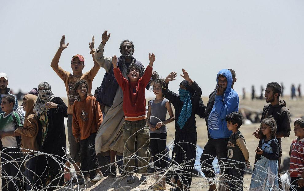 Сирийские беженцы на турецкой границе недалеко от города Таль Абьяд