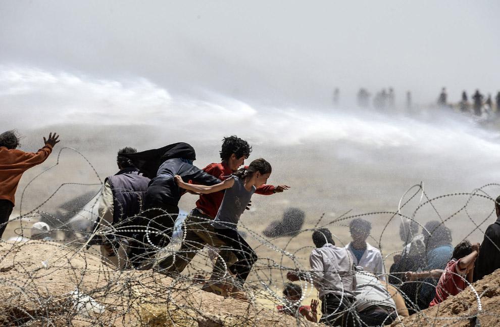 Турецкие пограничники отгоняют толпу водометами