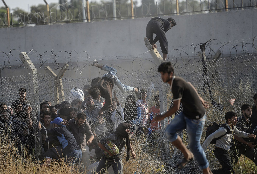 Сирийцы бегут из войны в Турцию, преодолевая забор