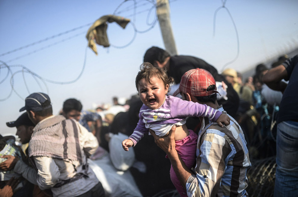 Сирийцы бегут от войны в Турцию, преодолевая пограничный забор