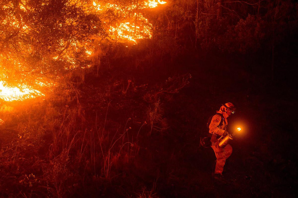 Пожарный готовится сделать контролируемый поджег