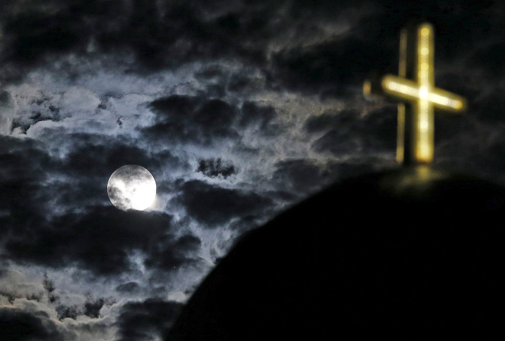 Луна поднимается над церковью на греческом острове Санторини