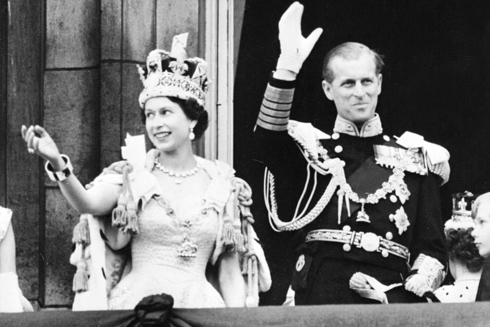 Королева Елизавета II в сопровождении принца Филиппа машет толпе с балкона Букингемского дворца