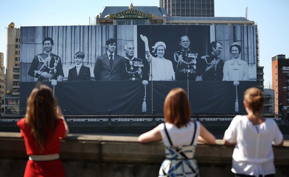 Рабочие возводят гигантскую фотографию королевской семьи на балконе Букингемского дворца