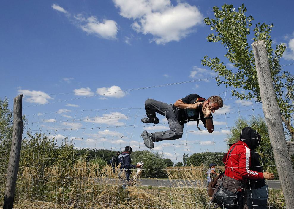 Мигранты перелезают через забор в Венгрию