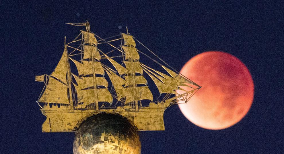 Вот как раз кровавая Луна видна над скульптурой парусника в Гамбурге, Германия