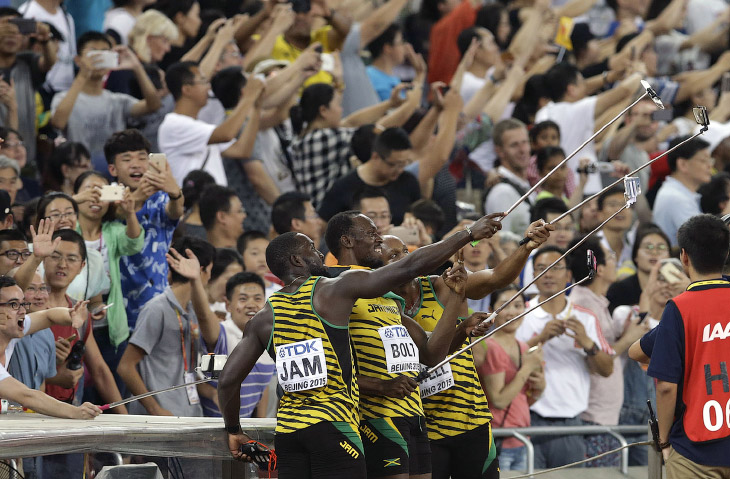 Ямайские бегуны с палками для селфи после эстафеты 4х100