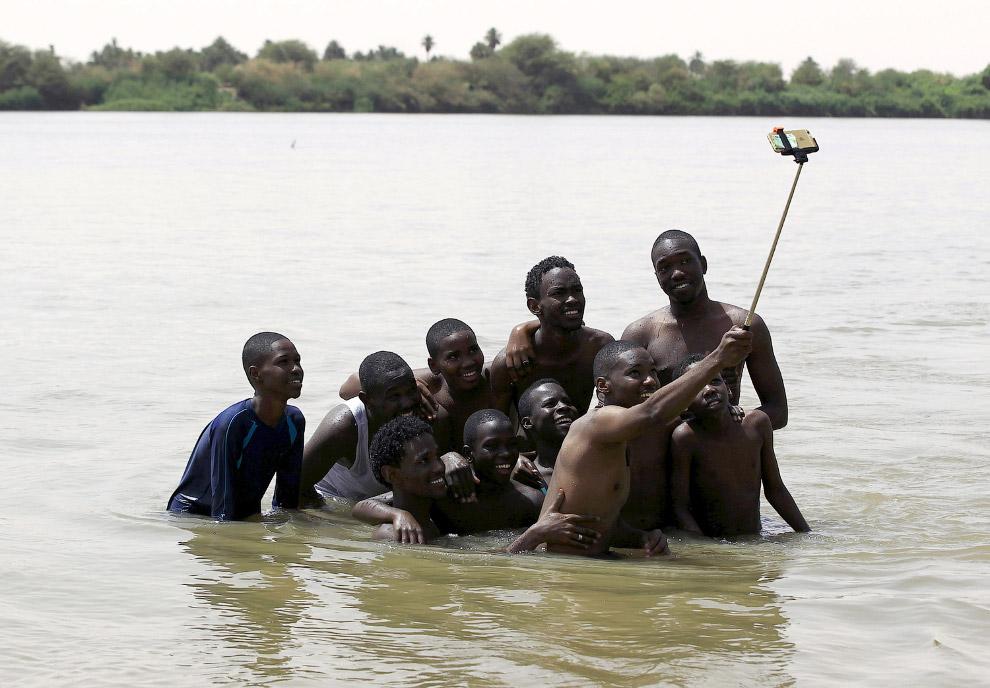 Продвинутые люди из Судана с 6-м Айфоном и палкой для селфи