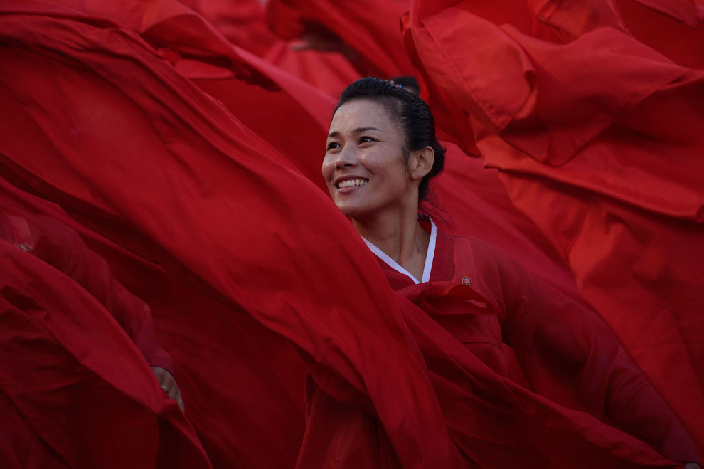 Танцоры в красных одеждах выступают на военном параде