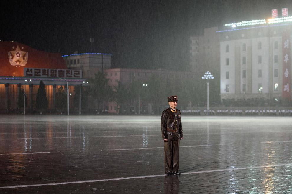 Северокорейский солдат стоит на посту под проливным дождем