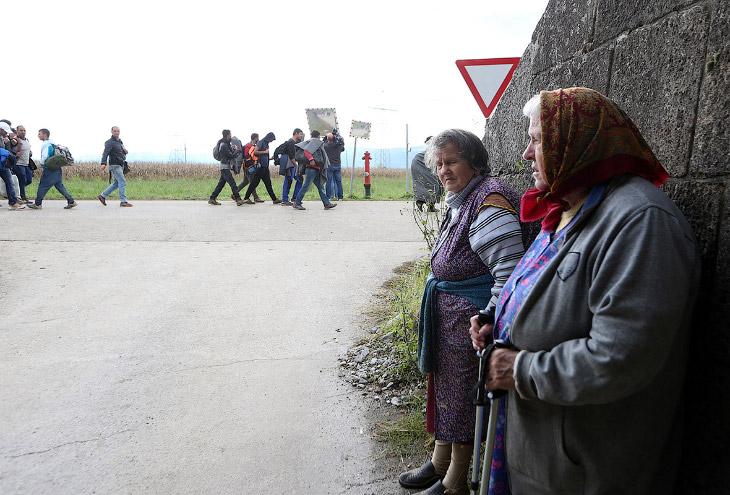 Местные жительницы с недовольным видом наблюдают за толпами, идущими по Брежице в Словении