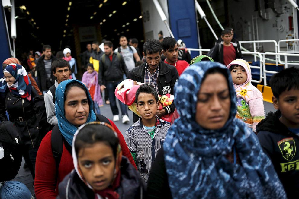 Мигранты прибывают в порт Пирей недалеко от Афин на борту пассажирского парома, идущего с острова Лесбос