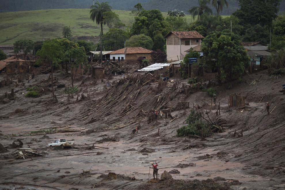 Спасатели с шестами. Здесь видно, как красная, токсичная грязь сметала на своем пути деревья