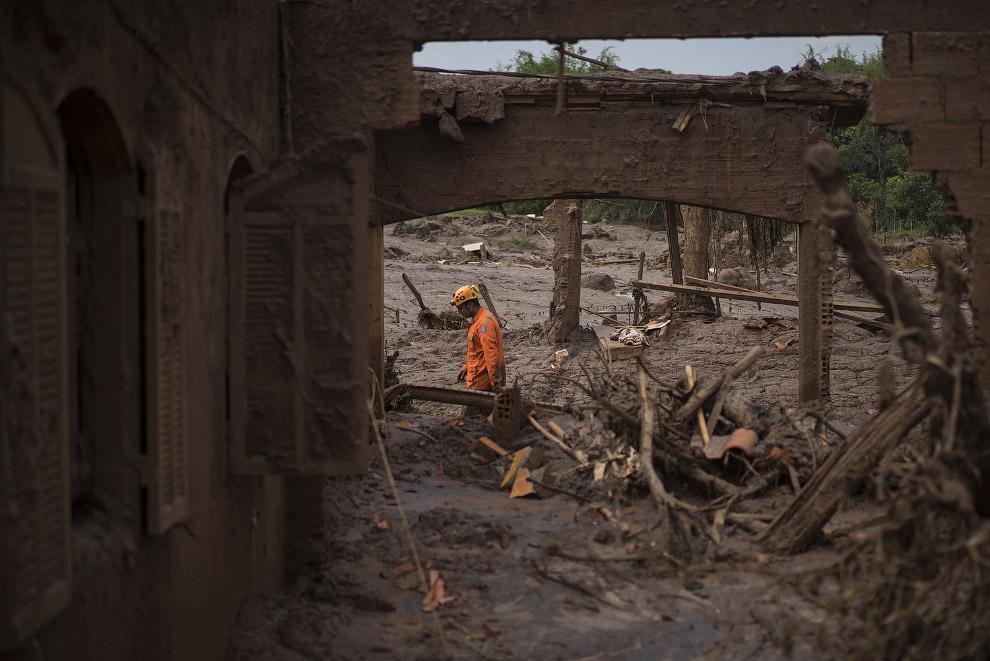 Спасатель в разрушенном селении Бенто-Родригес