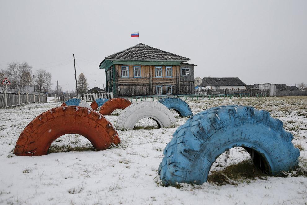 Шины, разукрашенные в цвет российского флага, перед зданием администрации в Санкино