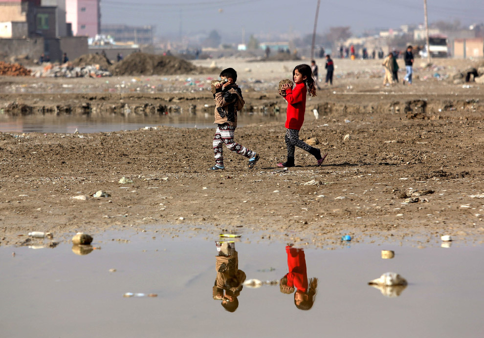 Дети играют в грязи на окраине Кабула