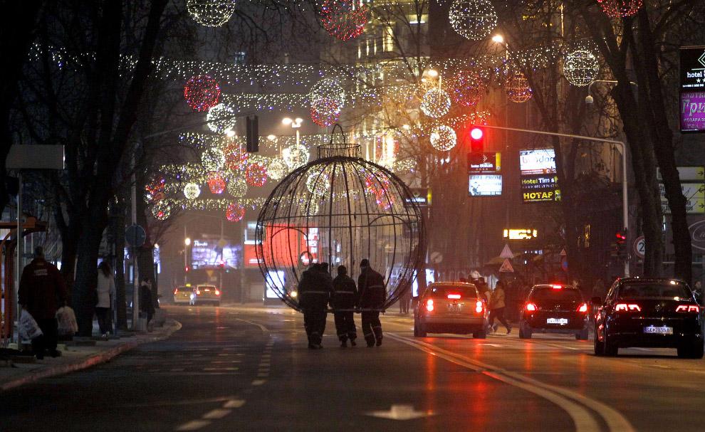 Работники несут новогоднее украшение по улице Скопье