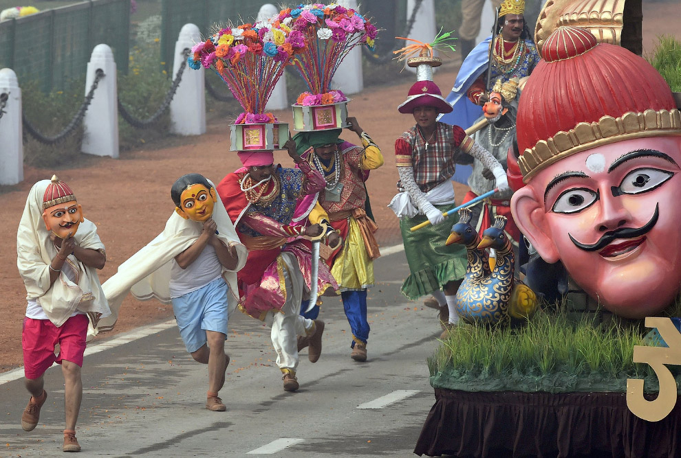 Танцоры в масках и костюмах на параде в Нью-Дели