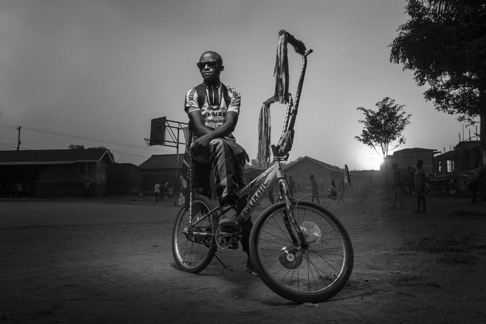 Парень на велосипеде в трущобах в Кампале, Уганда