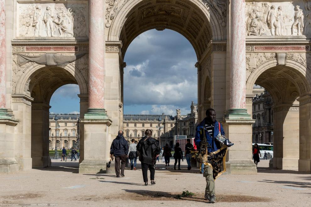 Нелегал на фоне барельефов Малой Триумфальной Арки и Лувра