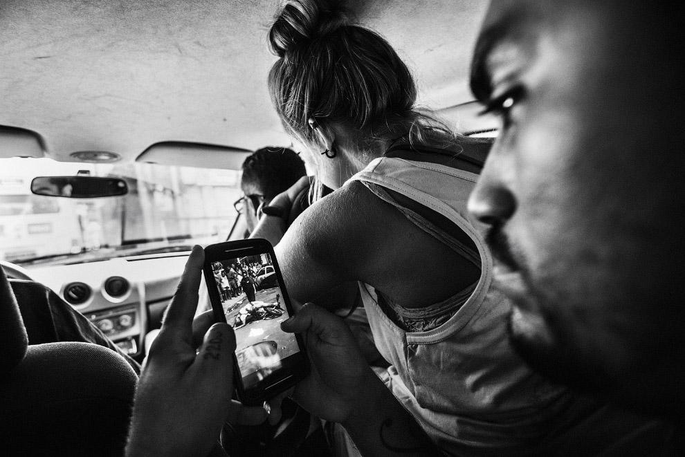В трущобах Рио-де-Жанейро человек рассматривает снимок 22-летнего таксиста, который был застрелен полицейским
