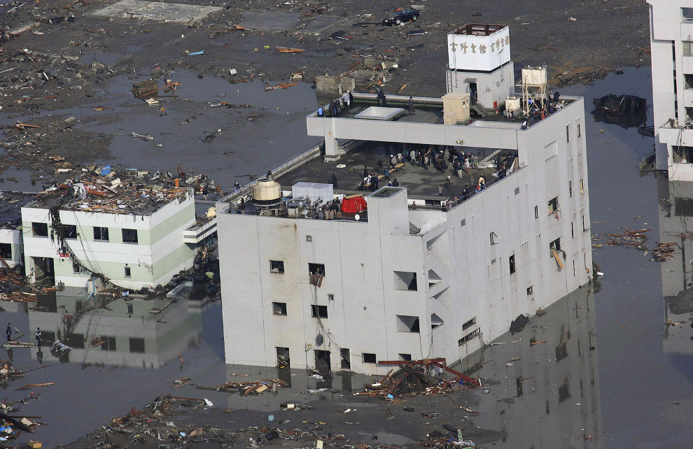 Люди собрались на крыше покосившегося знания, спасаясь от цунами
