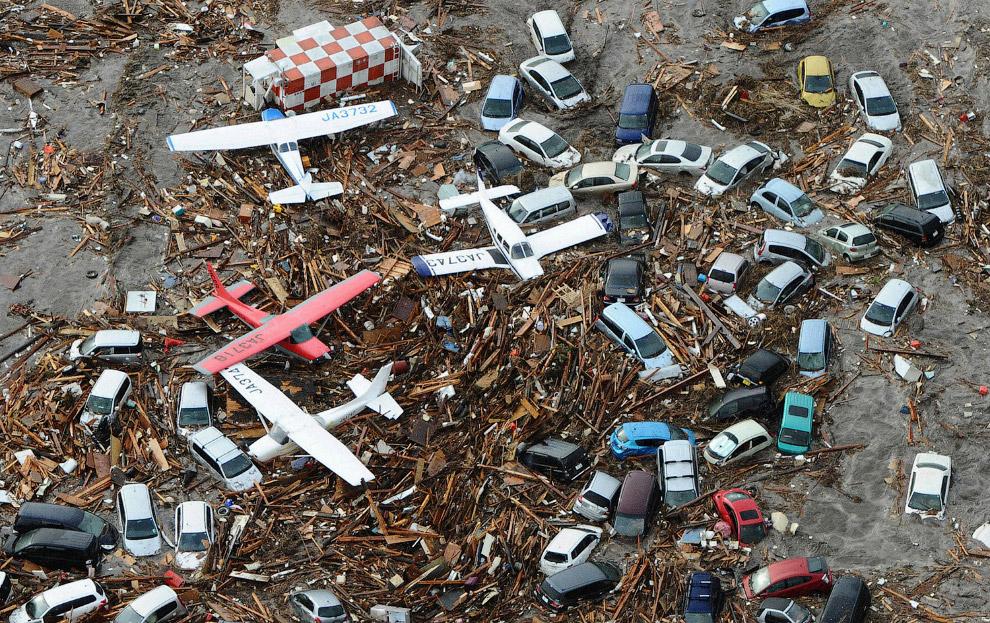 Автомобили, самолеты вперемешку с мусором недалеко от аэропорта Сендай