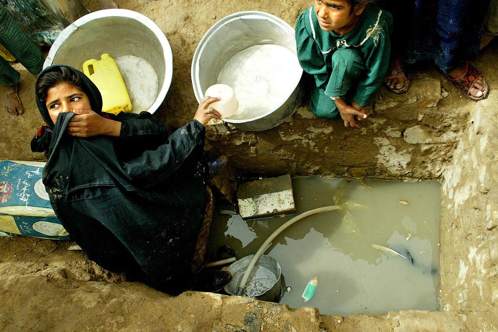 Сбор воды из какой-то дыры в земле недалеко от Багдада