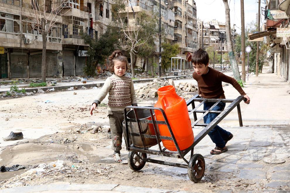 Поход за водой на разбомбленной улице в Алеппо, Сирия