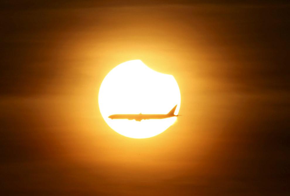 Частичное солнечное затмение и самолет в Сингапуре