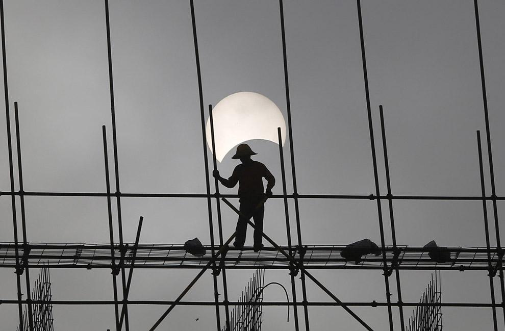 Солнечное затмение на строительной площадке в Пномпене, Камбоджа