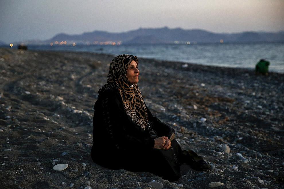 Слепая 70-летняя беженка из города Алеппо в Сирии сидит на пляже греческого острова Кос