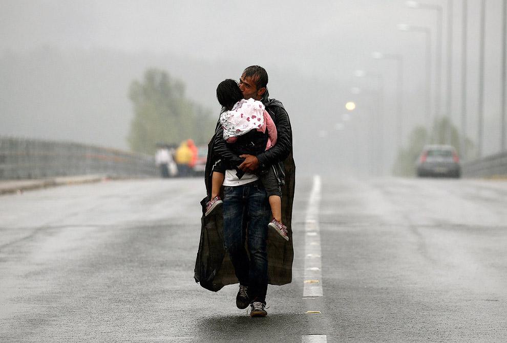 Сирийский беженец с дочкой на границе Греции с Македонией