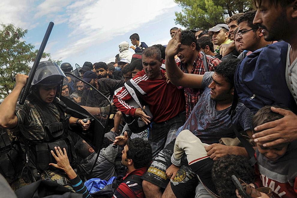 Полицейский Македонии борется с прорывающимися мигрантами на границе с Грецией