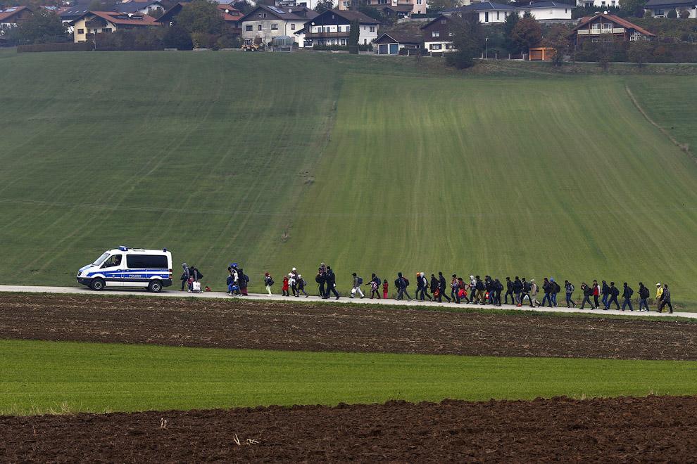 Мигранты в сопровождении полиции идут по немецкой земле после пересечения границы с Австрией
