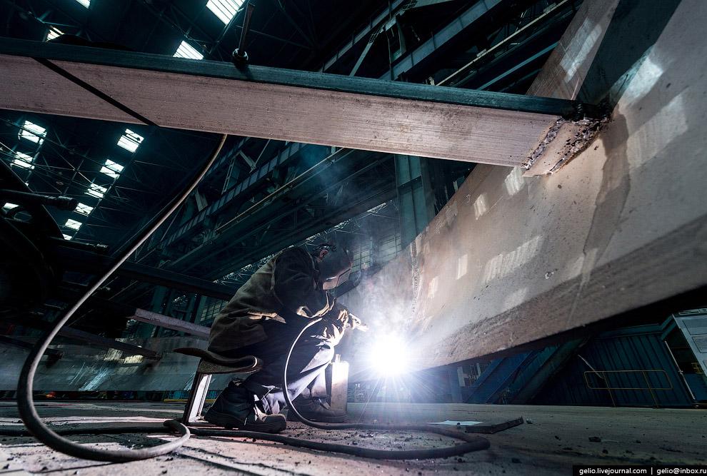 Ручная дуговая сварка элементов раскрепления на заготовке днища нефтеперерабатывающей колонны.