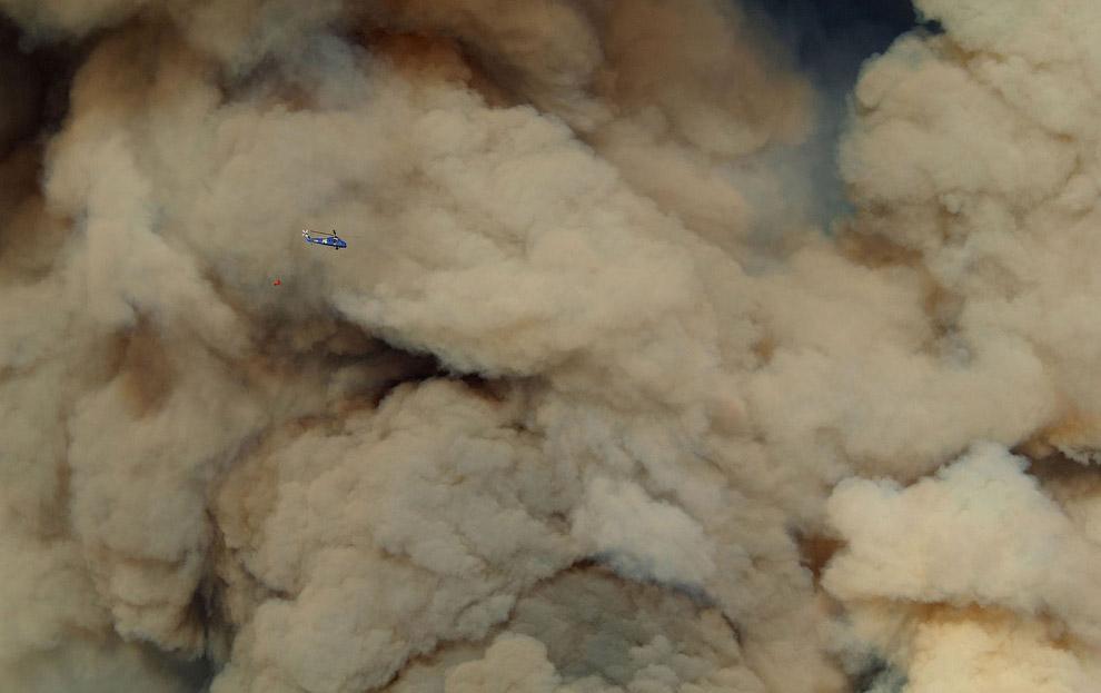 Огромные клубы дыма от лесного пожара и маленький пожарный вертолет