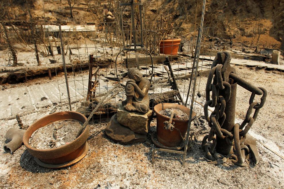 Пригорюнившаяся статуя Будды на месте сгоревшего дома