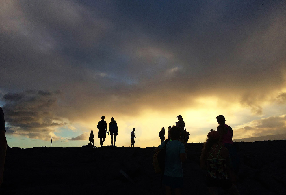 Туристы, бродящие среди потоков лавы
