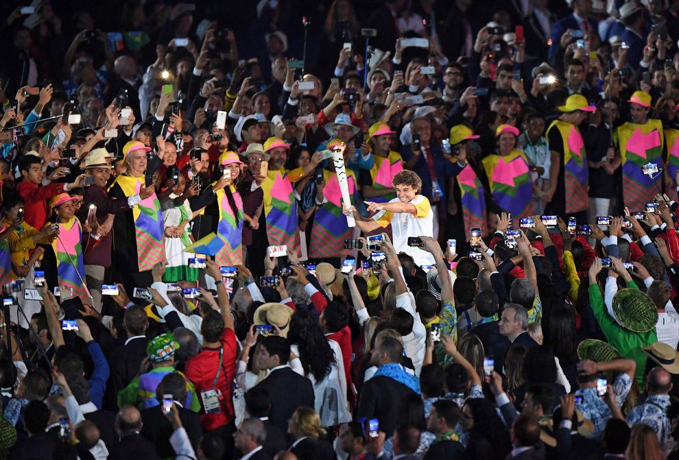 Бывший бразильский теннисист Густаво Куэртен несет олимпийский факел