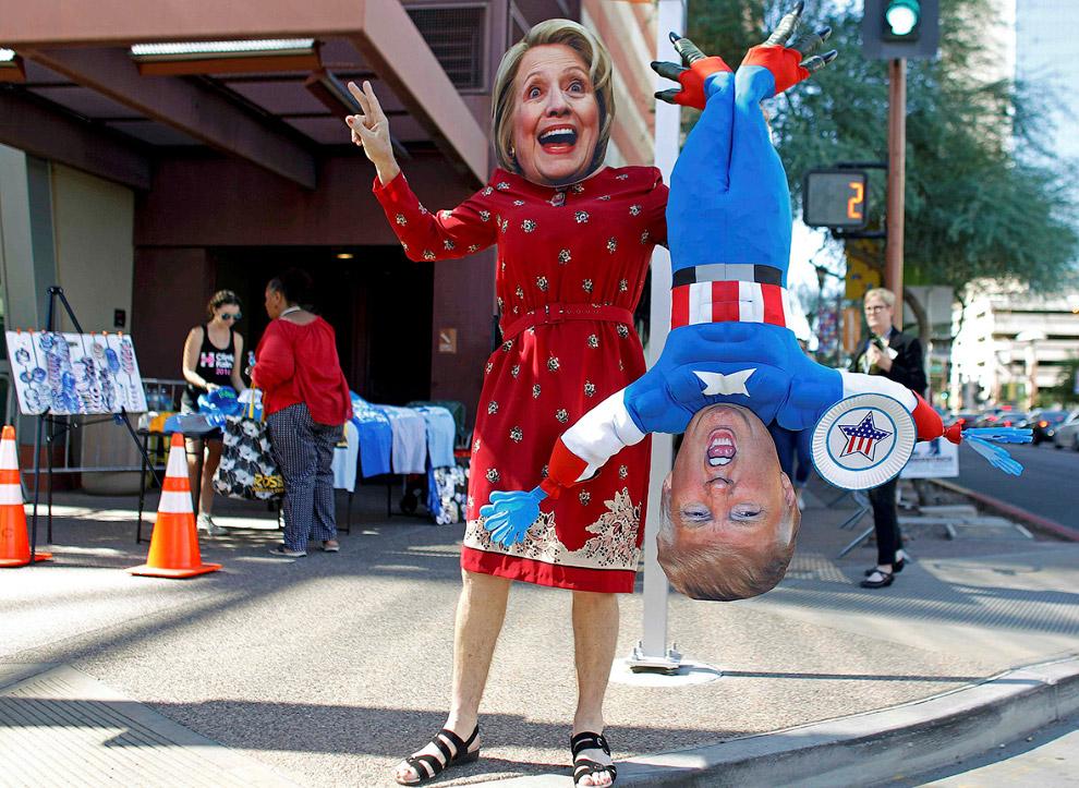 Человек в маске Хиллари Клинтон держит куклу Дональда Трампа в Фениксе, штат Аризона