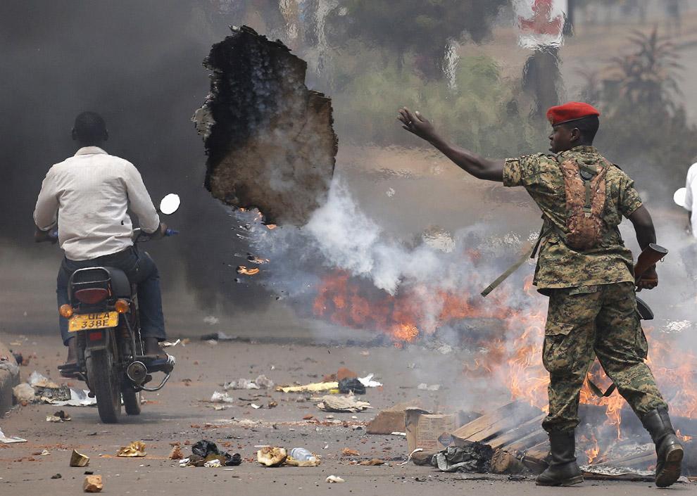 Угандийский солдат разбирает горящие баррикады во время столкновений в КампалеУгандийский солдат разбирает горящие баррикады во время столкновений в Кампале