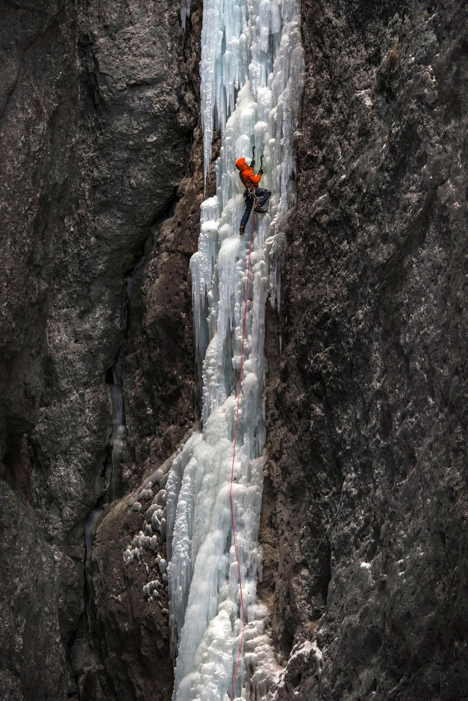 Альпинист карабкается на Spada Nella Roccia в итальянских Доломитах
