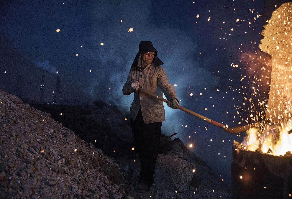 Рабочий загружает уголь в печь